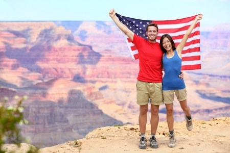 Happy young multiethnic couple cheering at Grand Canyon south rim during summer holidays  Stock Photo