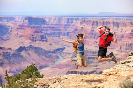 adventure holiday: Happy people jumping in Grand Canyon  Young multiethnic couple on hiking travel  Grand Canyon, south rim, Arizona, USA  Stock Photo