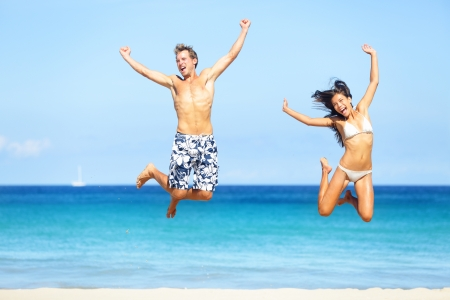bikini couple: Beach people - happy couple jumping in swimwear and bikini