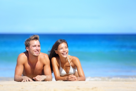 Happy multiethnic young couple lying on sand under sunny summer sun