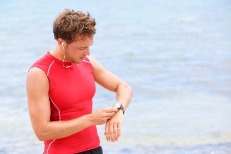 Corredor Atleta Hombre mirando el monitor del ritmo cardíaco reloj corriendo en la playa tomando un descanso en la compresión de la camiseta superior
