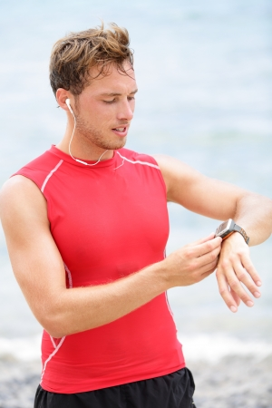 heart rate: Running man looking at heart rate monitor GPS watch Stock Photo