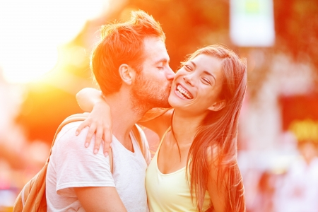 enamorados besandose: Pareja bes�ndose diversi�n Interracial pareja joven abrazando riendo en la fecha Foto de archivo