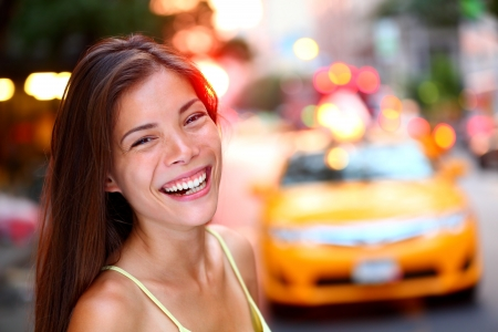 Happy New York City girl Woman smiling laughing joyful on Manhattan with yellow taxi cab in background