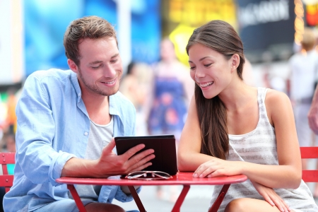 student travel: Multiethnic couple dating in New York City on Times Square  Man showing woman tablet pc smiling happy together  Stock Photo