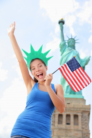old new york: Tourist at Statue of Liberty, New York, USA standing with american flag excited and happy Stock Photo