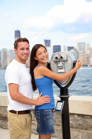 ellis: Happy romantic dating interracial couple sightseeing looking at Manhattan and New York City skyline from Ellis Island