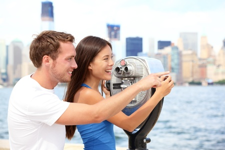 ellis: Tourists couple travel in New York  Beautiful young interracial young couple on travel looking at Manhattan and New York City skyline from Ellis Island Stock Photo