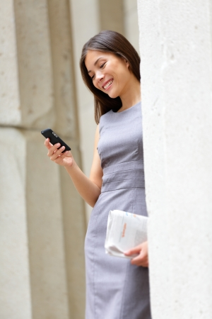 Young lawyer business woman professional texting text message on smart phone photo