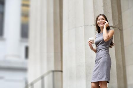 women talking: Lawyer businesswoman professional walking outdoors talking on cell smart phone drinking coffee