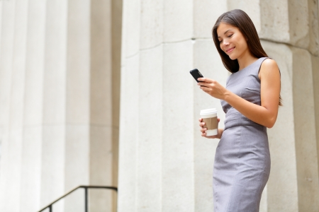 adult texting: Attorney - young asian woman lawyer looking at mobile smartphone and drinking coffee