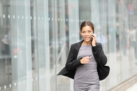 business communication: Business woman in motion, talking on mobile smart phone running outside on Manhattan, New York City