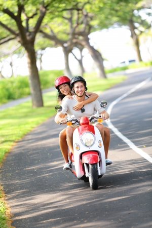 motor scooter: Scooter - couple driving in summer having fun on vacation holidays  Young happy interracial couple driving scooter  Asian woman, Caucasian man