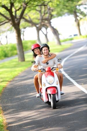 vespa: Scooter - pareja de conducción en verano se divierten en fiestas vacacionales feliz joven pareja interracial de conducir moto mujer asiática, hombre de raza caucásica Foto de archivo