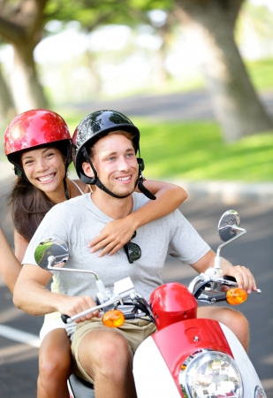 Free young couple on scooter on summer vacation holidays  Multiethnic happy couple having fun driving scooter together outdoor wearing helmets  Caucasian man, Asian woman  Stock Photo