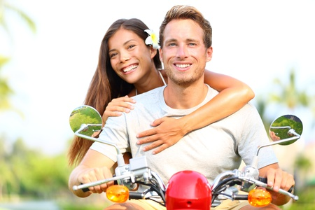 motor scooter: Happy young couple in love on scooter driving together  Multiracial couple having fun in the free outdoor  Smiling Caucasian man and Asian woman