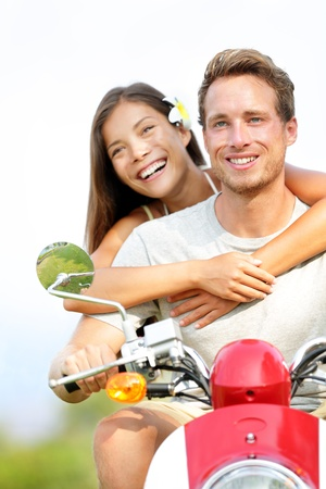 Young couple on scooter in love  Joyful mixed race couple having fun together outside driving motorcycle scooter  Asian woman, Caucasian man  Stock Photo - 17425291