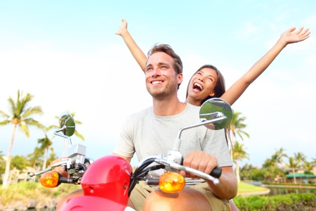 Happy free freedom couple driving scooter excited on summer holidays vacation  Young multiethnic couple, Asian woman, Caucasian man photo