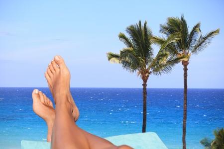 Desnudos pies femeninos descansando en un sillón reclinable con vistas a un mar azul tropical con palmeras conceptuales de unas vacaciones de verano o de viaje Foto de archivo