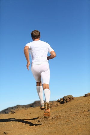 back country: Runner in nature running away in back view. Fit fitness athlete model trail running wearing compression clothes, shorts, socks etc. Stock Photo