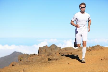 Uomo trail Runner in esecuzione in natura, paesaggio, scenico in abiti compressione. Giovane atleta in forma maschile di formazione fitness all'aperto per la maratona.