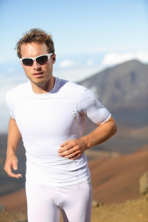 Running man. Male runner jogging outside in mountain landscape doing trail running in training for marathon race. Fit male fitness athlete in outdoor workout wearing sunglasses and compression clothes. photo