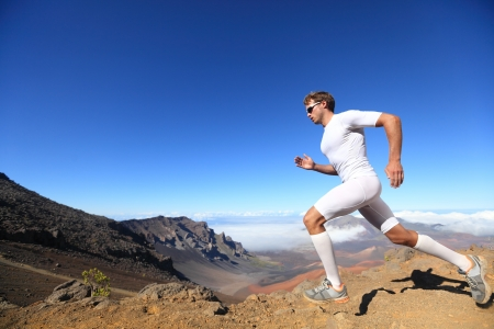 Running sport. Man runner sprinting outdoor in scenic nature. Fit muscular male athlete training trail running for marathon run. Sporty fit athletic man working out in compression clothing doing sprint. photo
