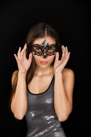 Mysterious young woman wearing carnival mask isolated on black background photo