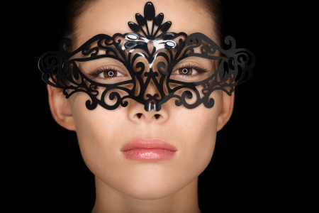 Beauty woman wearing carnival mask isolated on black background photo