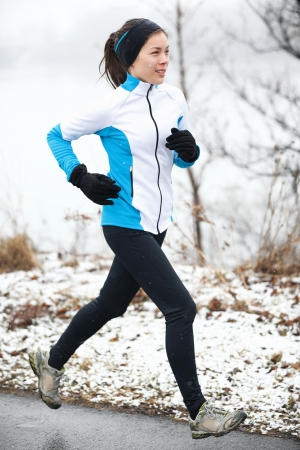 wintry weather: Fit slender young woman taking her daily exercise out jogging in a snowy landscape in winter