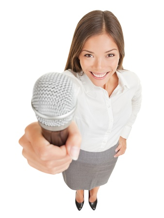high angle: Fun high angle perspective of a beautiful smiling young woman offering up a microphone Stock Photo