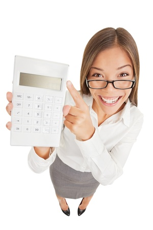 high angle: Fun high angle perspective of an attractive gleeful woman or accountant in glasses pointing to a calculator