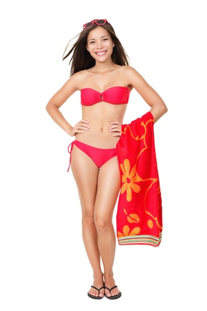 Bikini vacation holidays woman standing isolated holding red towel on white background Standard-Bild
