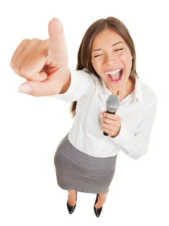 Fun high angle view of a passionate attractive young woman holding a microphone singing or making a point during a speech gesturing and pointing her finger at the camera isolated on white Stock Photo - 17600795