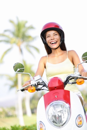 Free woman riding scooter happy. Beautiful asian woman joyful going on adventure riding scooter motorcycle on summer vacation holiday. Mixed race Asian Chinese  Caucasian girl. photo