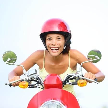 vespa: Mujer emocionada sobre esc�ter feliz. Retrato divertido de la mujer que conduc�a moto llevaba casco rojo. Hermosa raza mixta cauc�sica  asi�tica ni�a china.