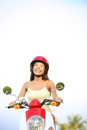 scooter: Woman on scooter thinking looking up at sky with copyspace. Happy multiracial woman driving scooter outdoor in summer. Stock Photo