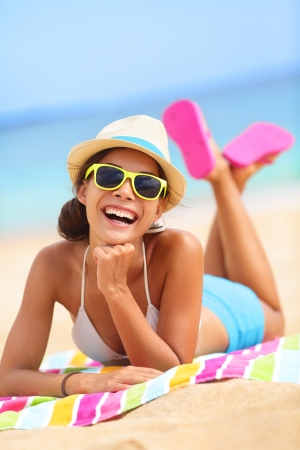 girl with towel: Beach woman laughing having fun in summer vacation holidays. Multiracial fashion hipster wearing sunglasses lying in the sand on colorful beach towel.