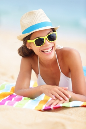 Beach travel woman smiling lying down on beach towel during summer vacation holiday. Mixed race Asian Chinese  Caucasian girl hipster wearing sunglasses and hat. photo