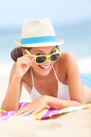 Woman on beach with sunglasses looking flirting at camera smiling happy and joyful during summer vacations holiday travel. Beautiful young multiethnic Asian Chinese  Caucasian hipster lying on beach towel. Stock Photo