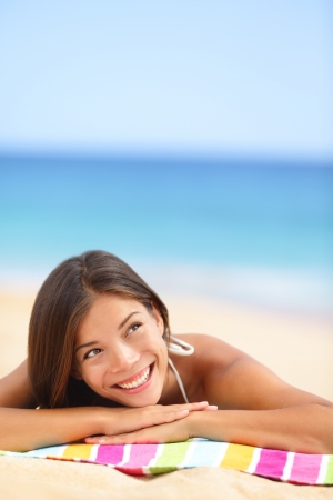 Beach woman thinking looking up at copyspace. Multiracial Asian Chinese / Caucasian female girl relaxing on beach towel smiling happy. Stock Photo - 17699296