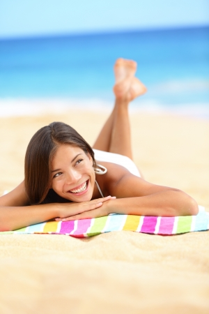 lying on side: Vacation beach woman lying down relaxing and looking to the side and up. Happy smiling girl in bikini lying on sand on beach towel during summer travel holidays.