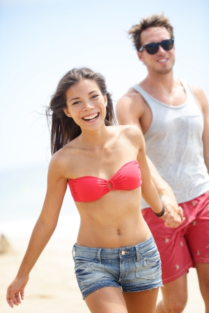 Happy young modern couple on beach. Interracial multiethnic cheerful couple walking on beach smiling joyful holding hands. Asian woman in bikini and Caucasian man. photo