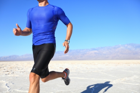 Sport - runner running and sprinting in desert. Athlete man during sprint run at great speed. Fitness man wearing compression clothes. photo