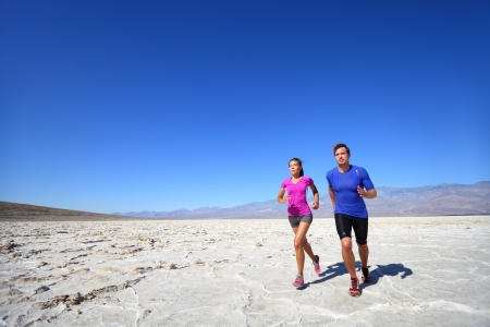 Athletes running sport fitness couple outdoor. Multiracial couple of runners training outdoors in fitness clothing under burning sun in desert. Caucasian man runner and Asian woman training. photo