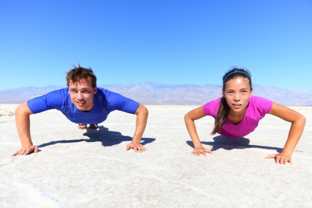 man working out: Sport - young fitness couple athletes doing push ups outdoors in desert nature landscape. Caucasian man sports model and Asian woman fitness model doing push-ups exercise under the burning sun. Stock Photo