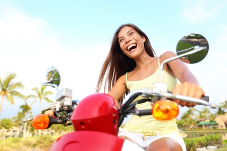 Happy free asian woman on scooter. Freedom concept with excited joyful asian woman driving scooter outdoor on summer vacation holidays. photo
