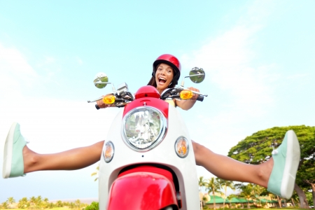 Funny happy free woman on scooter driving excited and cheerful. Mixed race Asian Chinese  Caucasian girl. Stock Photo
