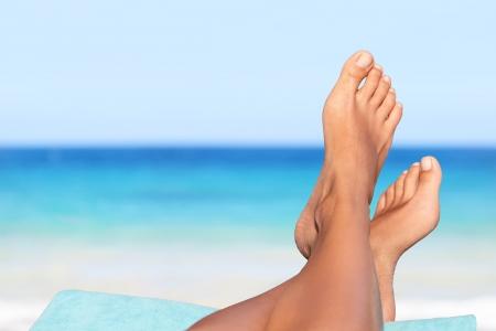 Les congés. Femme pieds gros plan d'une jeune fille de détente sur la plage sur le soleil en appréciant transat sur journée d'été ensoleillée.