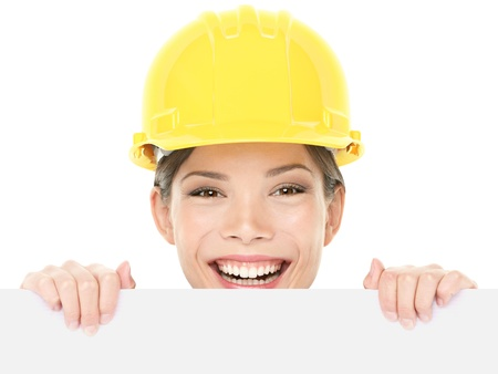 peaking: Construction worker  engineer woman showing sign wearing yellow hard hat. Happy young woman holding and peaking over white blank billboard sign card isolated on white background. Multiracial woman.